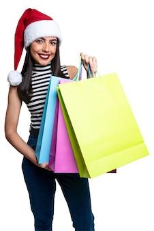 Santa claus frau, die einkaufstaschen hält, lokalisiert auf weißem hintergrund.