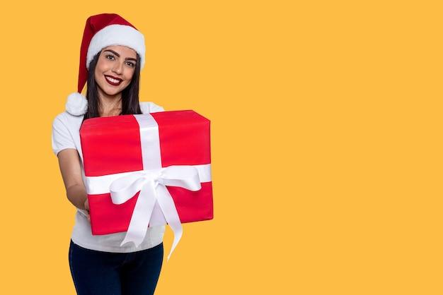 Santa claus frau hält ein geschenk, isoliert