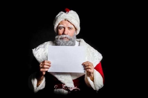 Santa claus hält ein leeres blatt in seinen händen auf einem schwarzen hintergrund