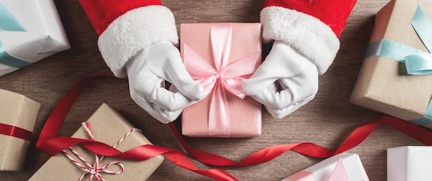 Santa claus hände mit gruppe von geschenkboxen.