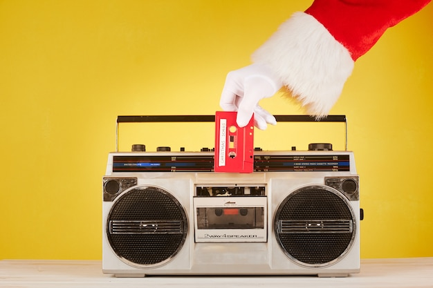 Santa claus hand, die ein audioband auf eine radiokassette legt