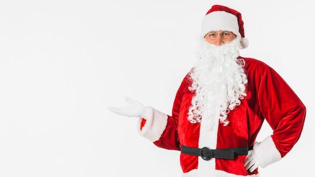 Santa claus im hut, der etwas mit der hand zeigt