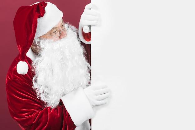 Santa claus im roten hut, der aus weißer wand heraus schaut