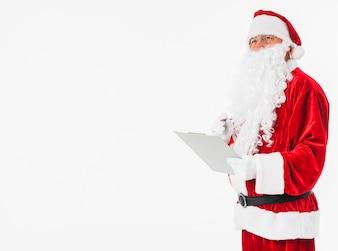 Santa Claus im roten Hutschreiben auf Papier mit Bleistift