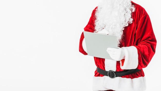 Santa claus im roten schreiben auf papier mit bleistift