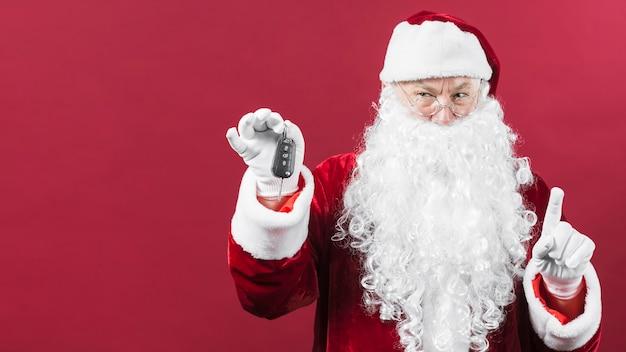 Santa claus in den gläsern, die in der hand autoschlüssel halten