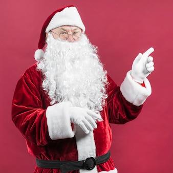 Santa claus in den gläsern mit der zeigehand