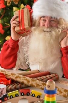 Santa claus in seiner werkstatt, die neue spielwaren herstellt