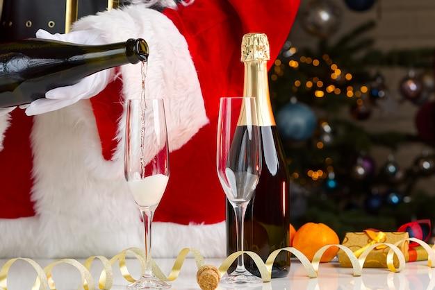 Santa claus kleid erwachsener, der champagner ausgießt. sekt durch gläser einschenken, feiern, urlaub beginnen, erfolgskonzept