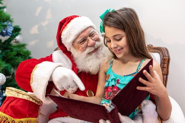 Santa claus liest einem kind auf seinem schoß ein bilderbuch vor