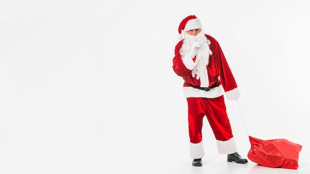 Santa claus mit dem sack, der geheime geste zeigt