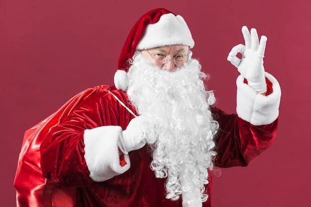 Santa claus mit dem sack, der okaygeste zeigt