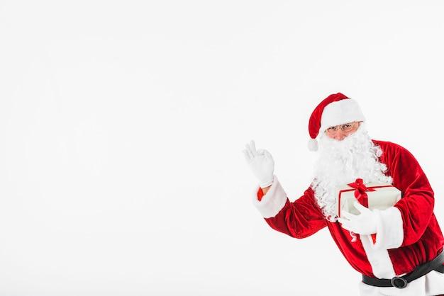 Santa claus mit der geschenkbox, die okaygeste zeigt