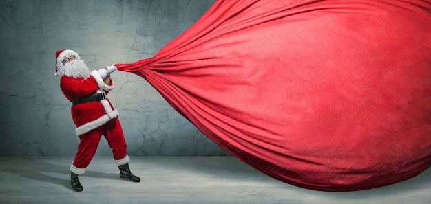 Santa claus mit großer tasche auf leerer anzeigenfahne mit kopienraum