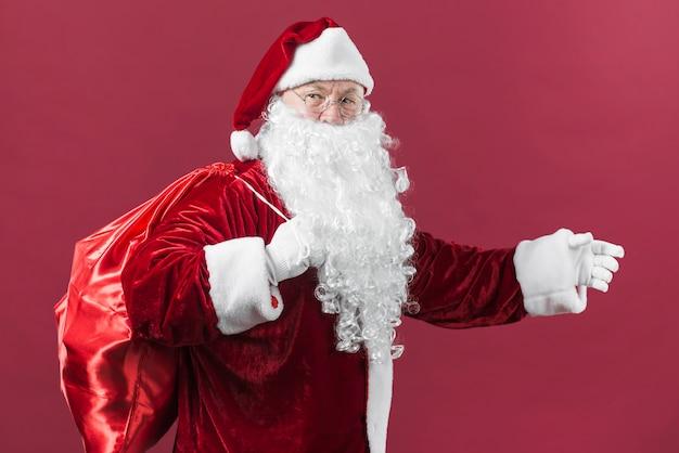 Santa claus mit sack geschenken auf rotem hintergrund