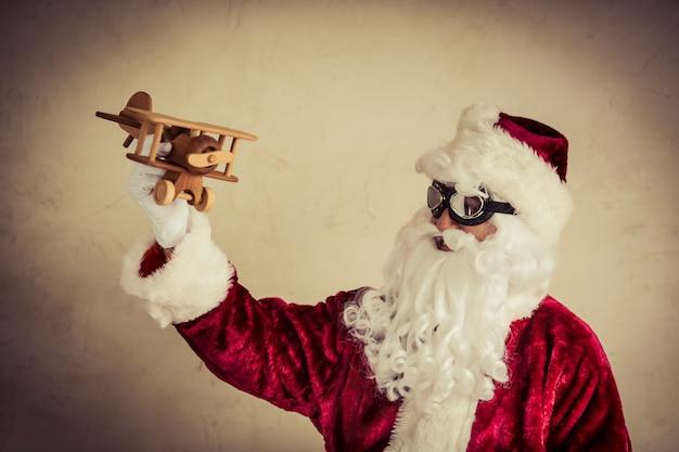 Santa claus senior mann spielt mit vintage holzflugzeug gegen grunge hintergrund weihnachten urlaub