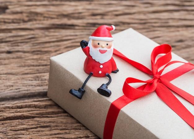 Santa claus sitzt auf einer geschenkbox auf einem bretterboden