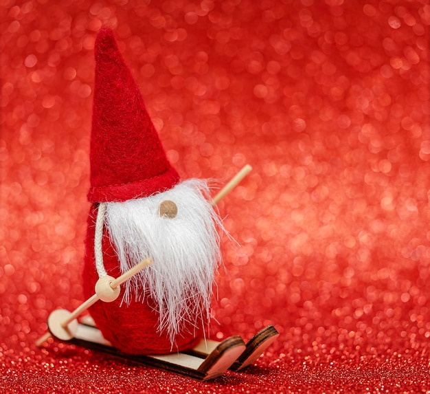 Santa claus skifahren auf rotem verschwommenem bokehhintergrund. kopierraum, selektiver fokus.
