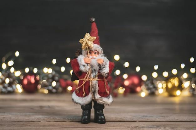 Santa claus-spielzeug hält personal mit stern, schnee, weihnachtsbälle