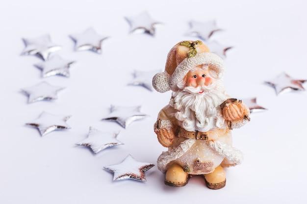 Santa claus statue mit silbernen sternen isoliert