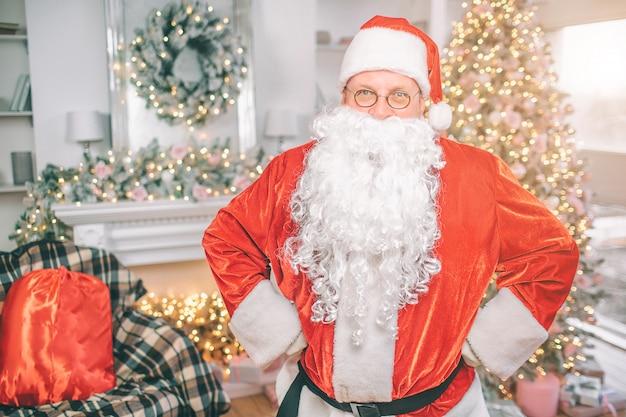 Santa claus steht in einem wohnzimmer mit weihnachtsdekoration