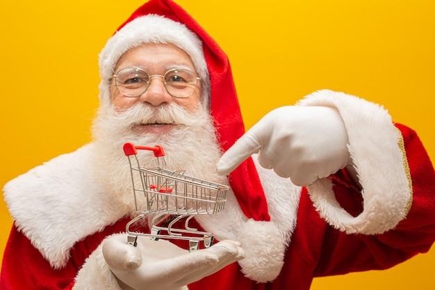 Santa claus und der supermarkt, er zeigt einen minikarren
