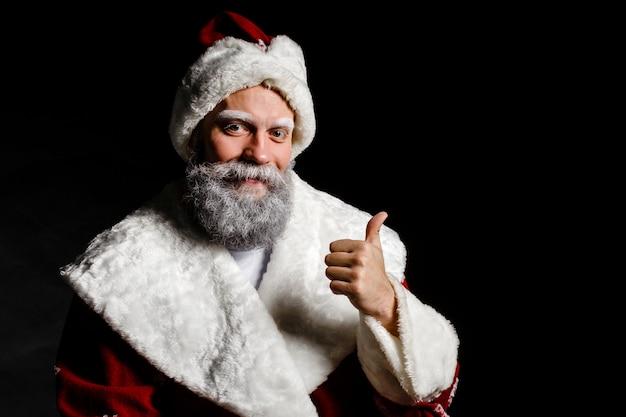 Santa claus zeigt klasse auf einem schwarzen hintergrund. weihnachtsmann anständig