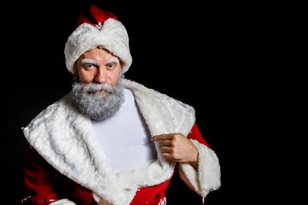 Santa claus zeigt seinen finger auf einem t-shirt auf einem schwarzen hintergrund