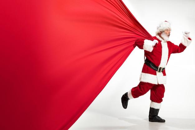 Santa claus zieht riesige tasche voller weihnachtsgeschenke isoliert auf weißem hintergrund. kaukasisches männliches modell in traditioneller tracht. neujahr 2020, geschenke, feiertage, winterstimmung. copyspace für ihre anzeige.