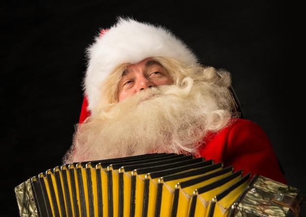 Santa claus zu hause und spielt musik auf akkordeon.