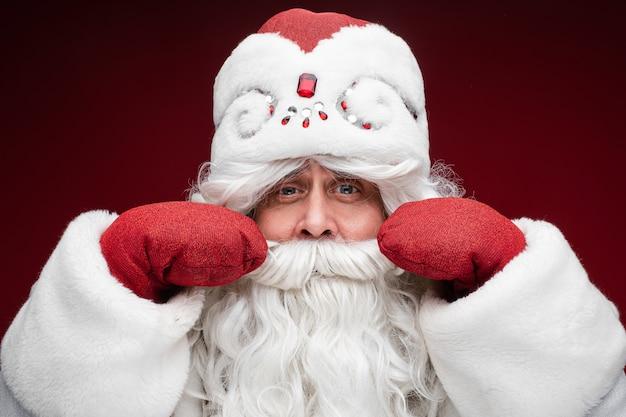 Santa grauhaariger älterer mann in handschuhen zeigt seinen schnurrbart