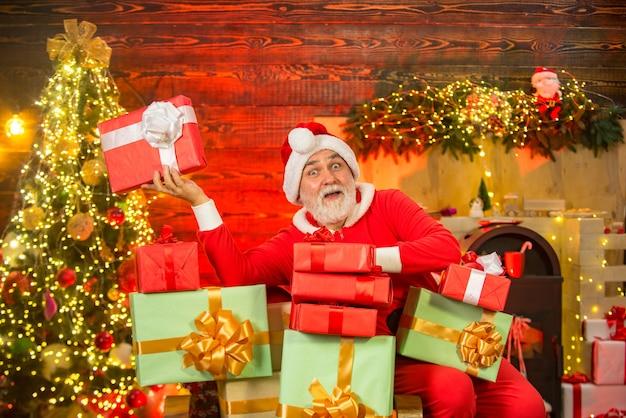 Santa großvater mit einem weißen bart posiert auf dem weihnachtshölzernen hintergrund porträt eines reifen ...