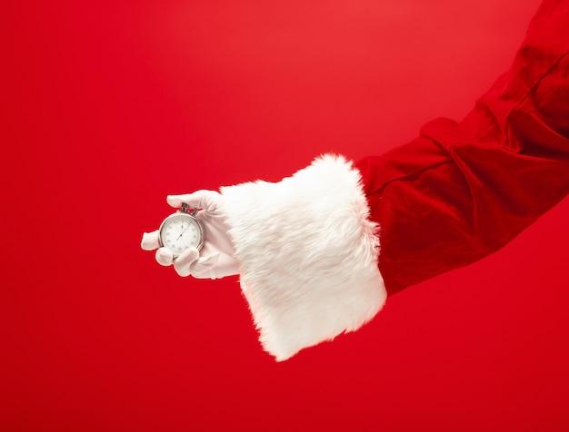 Santa hält eine stoppuhr auf rotem hintergrund. die jahreszeit, winter, feiertag, feier, geschenkkonzept