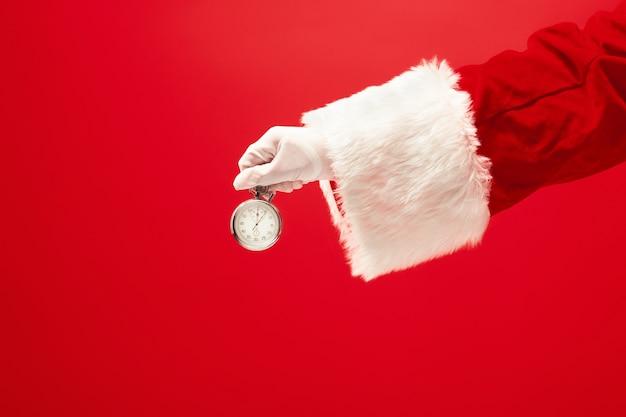 Santa hält eine stoppuhr auf rotem hintergrund. jahreszeit, winter, feiertag, feier, geschenkkonzept
