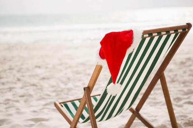Santa hat gehalten auf leeren strand stuhl
