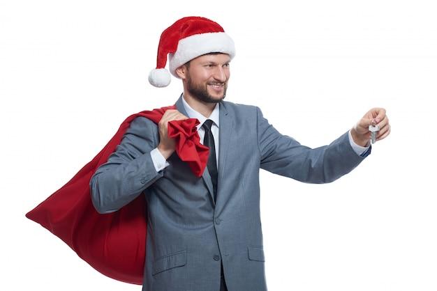 Santa klausel in der grauen suite, rote kappe, die volle tasche über schulter hält, lächelt, wegschaut, schlüssel gibt.