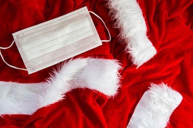 Santa kostüm stoff mit weißer sicherheitsmaske hintergrundtextur, weihnachtskonzept und covid-19 konzept 2020, nahaufnahme
