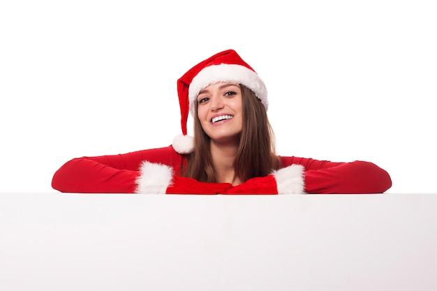 Santa mädchen, das sich auf leeres brett stützt