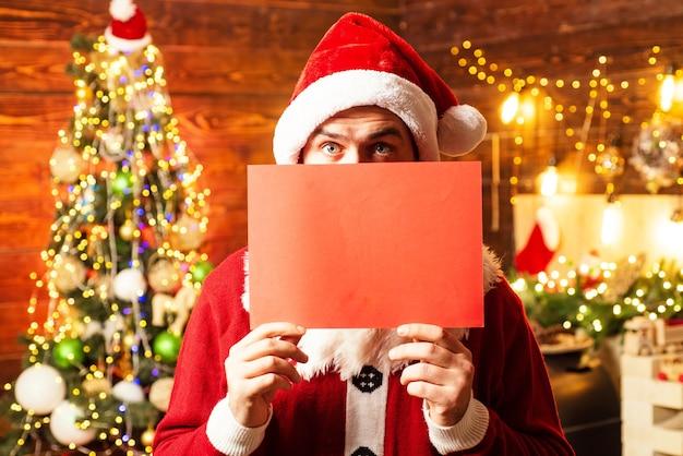 Santa mann posiert mit leerer roter karte
