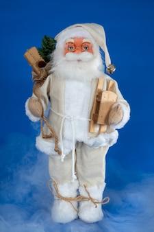 Santa marionettenpuppe mit holzschlitten gegen blau mit nebligem rauch