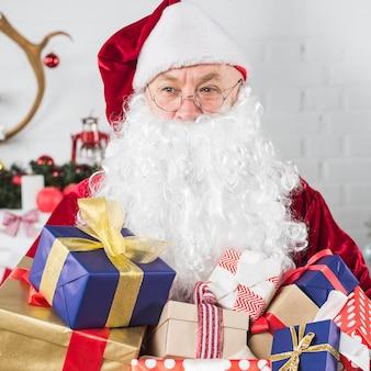 Santa mit geschenkboxen in händen