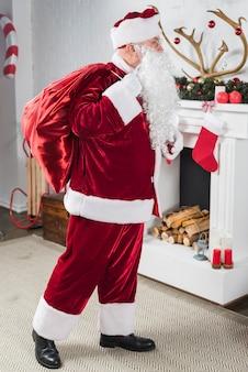 Santa mit großen sack geschenke hinter zurück in der nähe von kamin