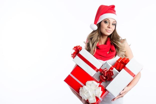 Santas helfer. junges lächelndes mädchen mit geschenken in den händen in einer weihnachtsmannmütze lokalisiert auf weiß