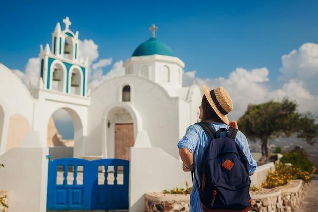 Santorini-inselreisender, der griechische kirchenarchitektur in akrotiri erforscht. frauentourist, der während der ferien geht