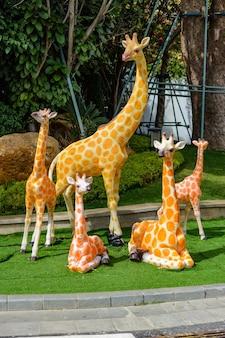 Sanya, hainan, china - 20. februar 2020: bunte statuen der giraffenfamilie auf der straße von sanya am bewölkten tag.