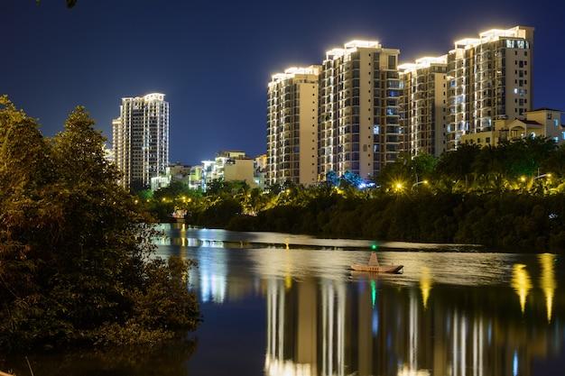 Sanya, hainan, china - 25. januar 2020: nachtansicht der stadt sanya mit hellen mehrfarbigen beleuchtungsgebäuden, strukturen, straßen, gehwegen, masten, brücken.
