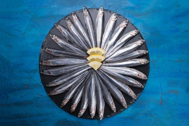 Sardellen in form eines kreises auf einem schwarzen stein. meeresfrüchte. kleiner meeresfisch