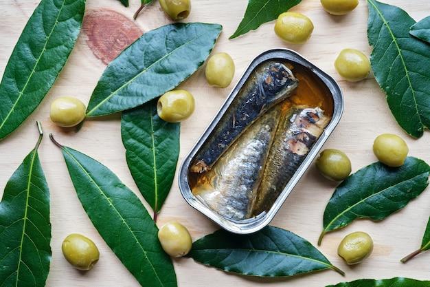 Sardinenform in öl von oben gesehen mit oliven und lorbeerblättern