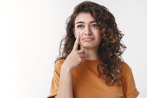 Sarkastisches süßes, lockiges armenisches mädchen hält die zeigefingerkamera, als würde man tränentropfen zeigen, die verärgert sind