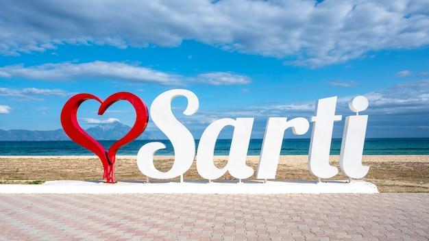 Sarti mit rotem herzzeichen an der ägäisküste mit wasser und berg, griechenland